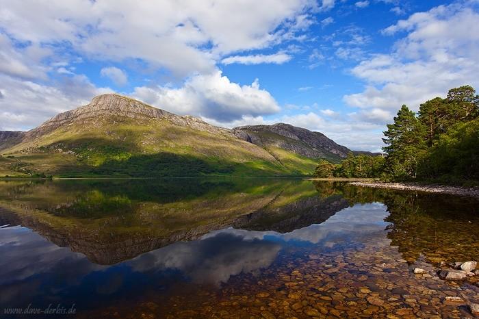 Spiegelung eines Bergs im windstillen, whiskey-farbenen Wasser des Loch Maree