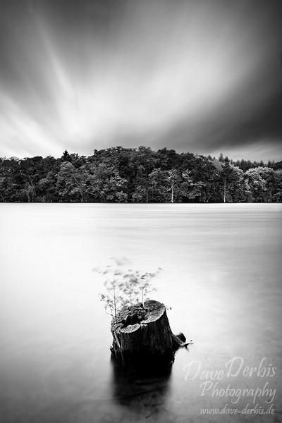 Langzeitbelichtung von ziehenden Wolken über einem See