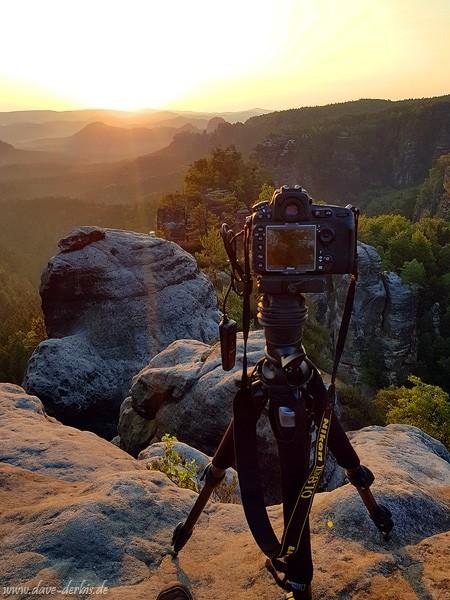 Kamera und Stativ blicken am Abgrund in die Sonne