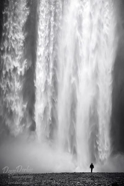 Person steht vor gewaltigem Wasserfall in Island