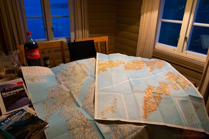 Reiseplanung mit Karten und Laptop