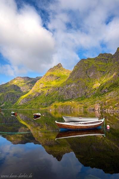 Spiegelung mit Booten im windstillen See in Norwegen